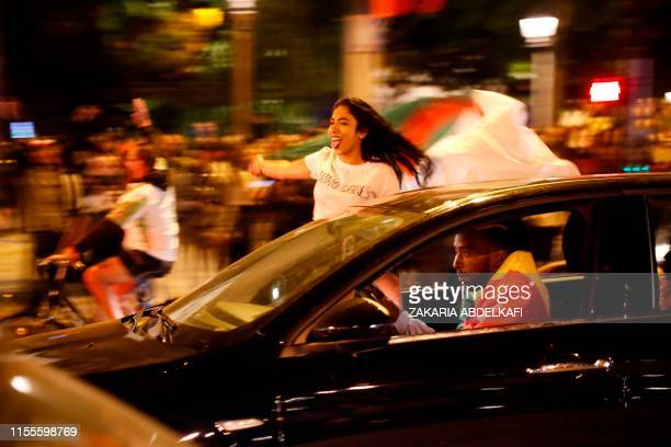 Algeria supporters with the country's national flag celebrate after Algeria won the 2019 Africa Cup of Nations semifinal football match against...