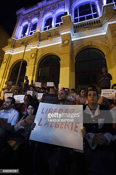 Algerian artists and journalists hold placards during a demonstration outside the National Theatre in Algiers late on July 1 asking for the release...