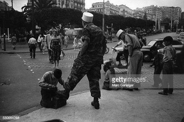 Algerian Boys Clean Boots of Colonial Paratroopers