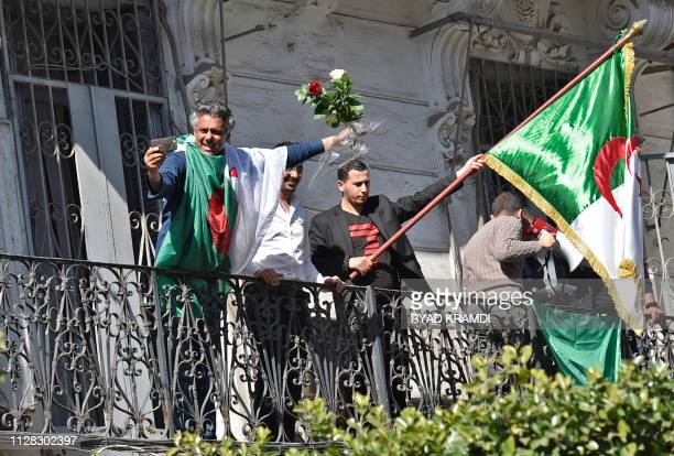 Algerian businessman and political activist Rachid Nekkaz uses a cell phone to film himself holding on to red and white roses while on a balcony as...