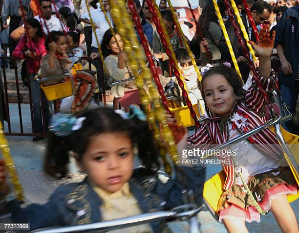 Algerian children enjoy a ride at a park in Algiers city 14 October 2007 on the occaision of EidalFitr The threeday festival which begins after the...