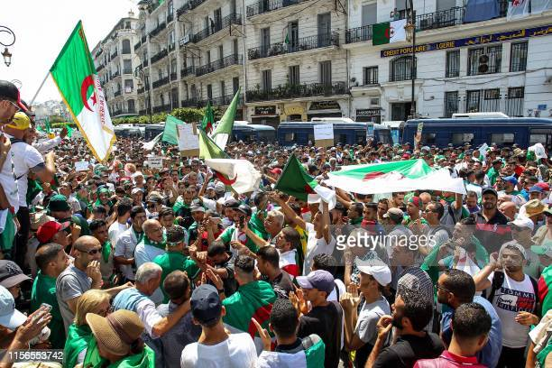 Algerian demonstrators chant slogans as they gather in the streets of the capital Algiers against the ruling class amid an ongoing political crisis...