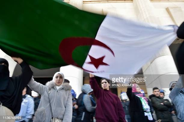 Algerian demonstrators hold a giant national flag during a demonstration against Algeria's president's candidacy for a fifth term on February 22 2019...