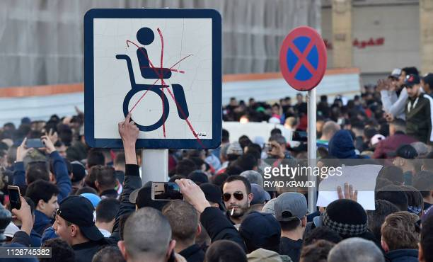 TOPSHOT Algerian demonstrators hold a placard with the symbol of a man on a wheelchair during a demonstration against Algeria's president's candidacy...