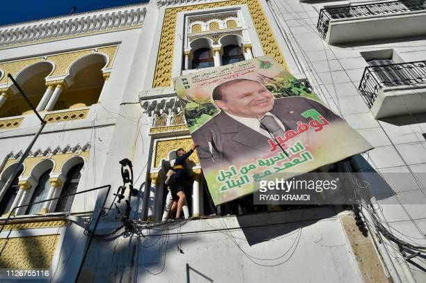 TOPSHOT Algerian demonstrators tear down a large billboard with a picture of their current President Abdelaziz Bouteflika on it during a...