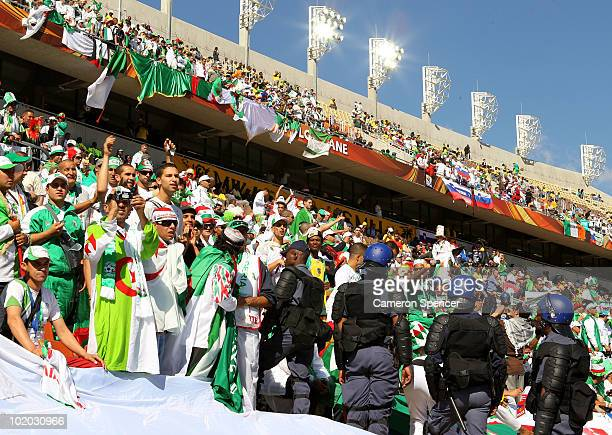 Algerian fans enjoy the atmosphere as South African security look on during the 2010 FIFA World Cup South Africa Group C match between Algeria and...