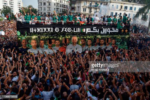 Algerian fans line the streets to see their national team take part in an open-top bus parade in the capital Algiers on July 20 following their...