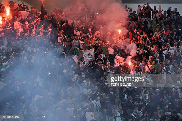 Algerian fans react and light flares during a friendly soccer match against Tunisia in Rades Olympic Stadium in Tunis on January 11 2015 AFP PHOTO/...