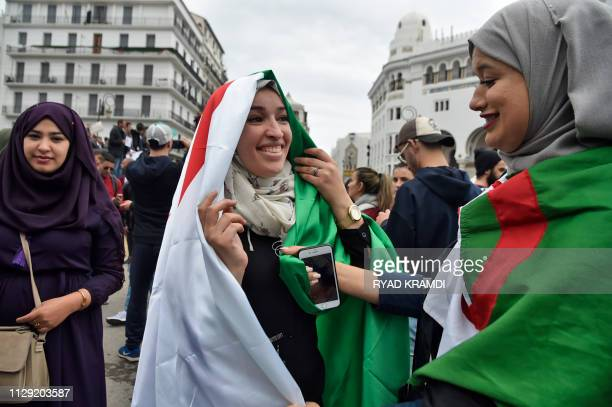 Algerian female protesters wear their national flags as they demonstrate against their ailing president's bid for a fifth term in power in Algiers on...