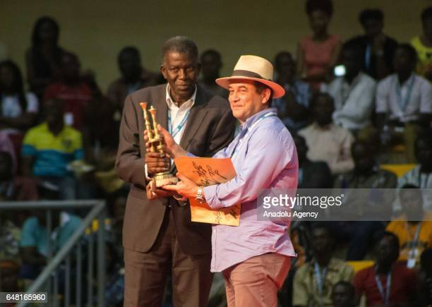 Algerian film director Lotfi Bouchouchi holds the award after receiving the during the award ceremony on the last day of 25th Panafrican FESPACO Film...