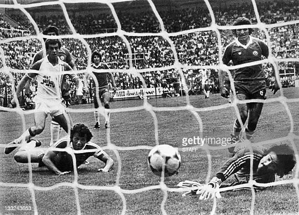 Algerian forward Salah Assad scores his second goal as Chilean defender Rodolfo Dubo and goalkeeper Mario Osben watch the ball go into the net 24...