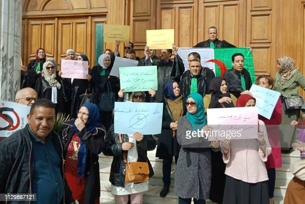 Algerian judges hold placards as they protest against their ailing president's bid for a fifth term in power in the northeastern city of Annaba on...