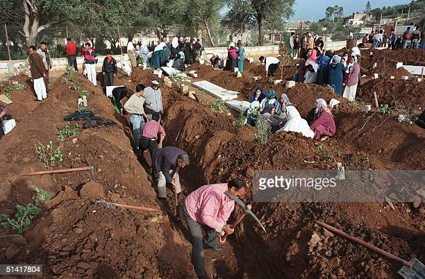 Algerian men dig trenches 13 January to burry the victims of the country's latest massacre in the Sidi Hamed cemetery near the capital Algiers The...