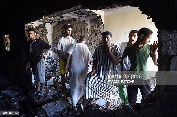 Algerian men from the Arab community look at the damage in a house on July 9 following clashes between Berbers and Arabs in the town of Guerara in...