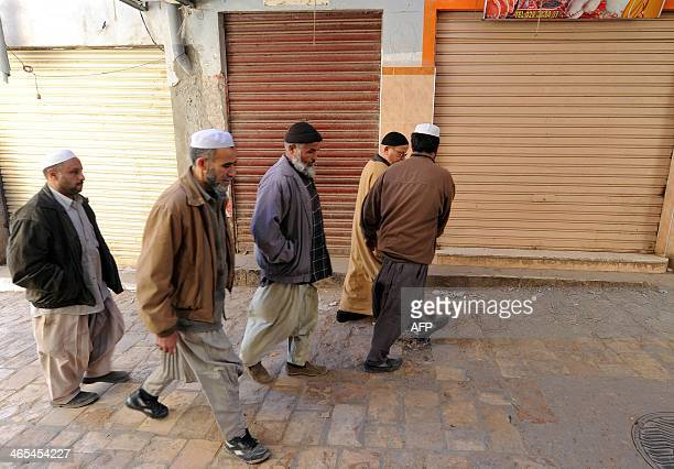 Algerian men from the Mozabites community a Berber minority group which adheres to the Ibadi faith an offshoot of Shiite Islam walk past closed shops...