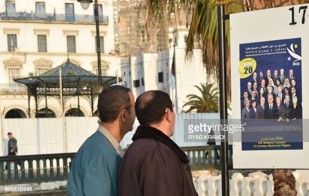 Algerian men look at electorial campaign posters for the upcoming legislative elections in Algiers' Martyrs Square as the official start of...