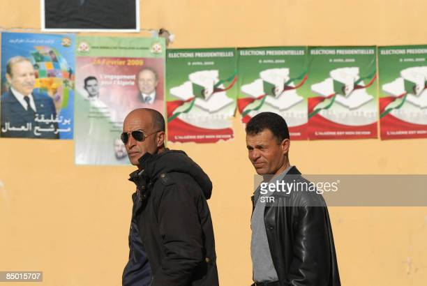 Algerian men walk past posters supporting President Abdelaziz Bouteflika's candidacy in the Presidential elections and welcomig his visit his visit...