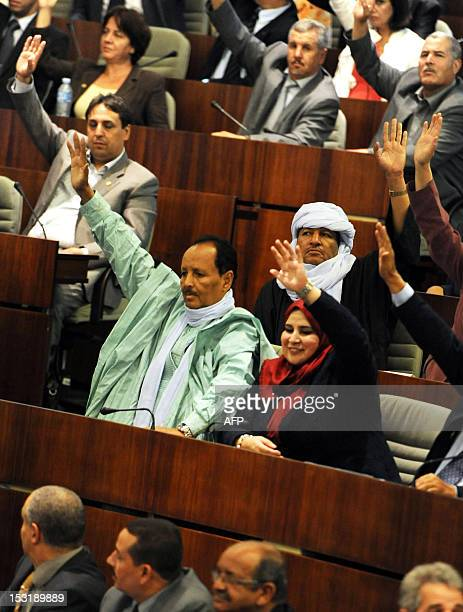 Algerian MP vote during a parliamentary session at the National Assembly in Algiers on October 1 to adopted an action plan for the new government...