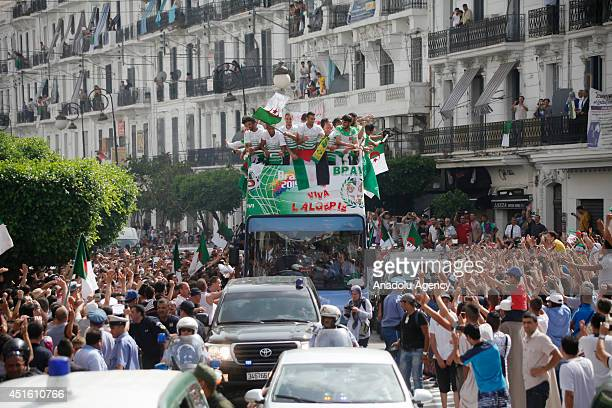 Algerian national soccer team players stand atop a bus greet fans as they tour the city upon their arrival from Brazil after they eliminated from...