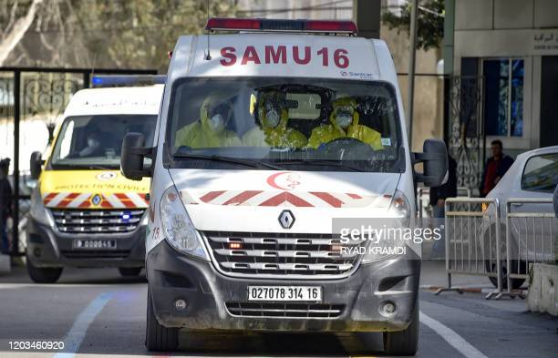 Algerian paramedics wearing protective outfits are pictured inside an ambulance in front of El-Kettar hospital in the capital Algiers on February 26,...