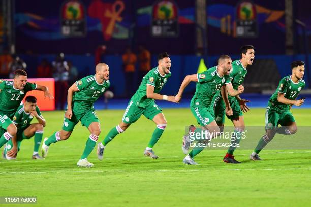 Algerian players celebrate after winning the 2019 Africa Cup of Nations quarter final football match between Ivory Coast and Algeria at the Suez...