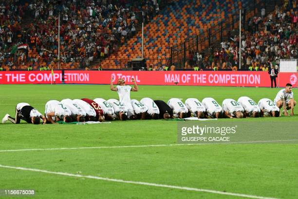 Algerian players pray as they celebrate after winning the 2019 Africa Cup of Nations Final football match between Senegal and Algeria at the Cairo...