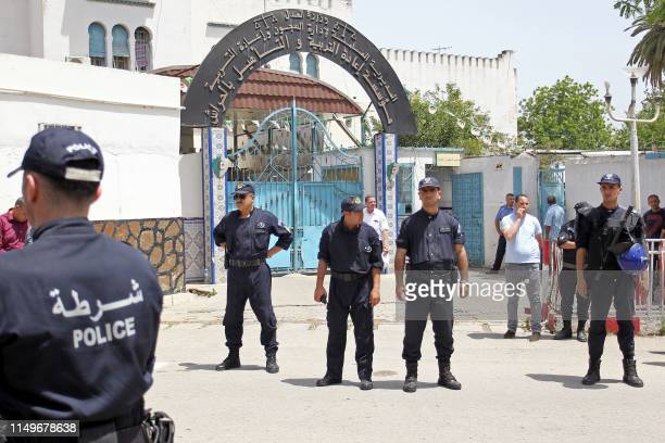 Algerian policemen stand guard the street prior to the arrival of Algeria's former prime minister Abdelmalek Sellal who's being driven to custody at...