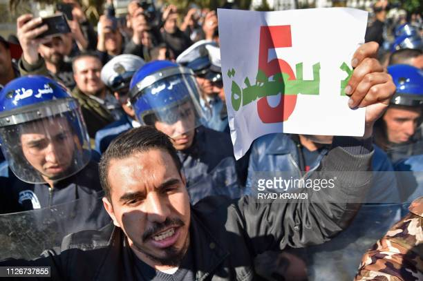 Algerian policemen surround protestors during a demonstration against Algeria's president's candidacy for a fifth term on February 22 2019 in Algiers...