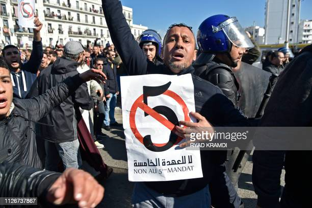 TOPSHOT Algerian policemen surround protestors during a demonstration against Algeria's president's candidacy for a fifth term on February 22 2019 in...