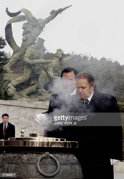 Algerian President Abdelaziz Bouteflika burns incense during a visit to the National Cemetery in Seoul 09 December 2003 Bouteflika arrived here 08...