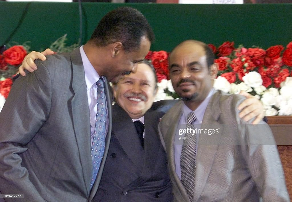 Algerian President Abdelaziz Bouteflika (C) hugs Eritrean President Issaias Afeworki (L) and Ethiopian prime minister Meles Zenawi 12 December 2000, during the signing of a peace accord to end more than two years of war between Ethiopia and Eritrea over disputed territory 12 December 2000, in Algiers. The cermony comes after a initial ceasefire deal signed in June between the Horn of Africa neighbours, putting a stop to bloody border fighting which has claimed tens of thousands of lives.