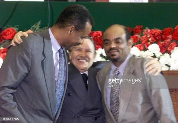 Algerian President Abdelaziz Bouteflika hugs Eritrean President Issaias Afeworki and Ethiopian prime minister Meles Zenawi 12 December 2000 during...
