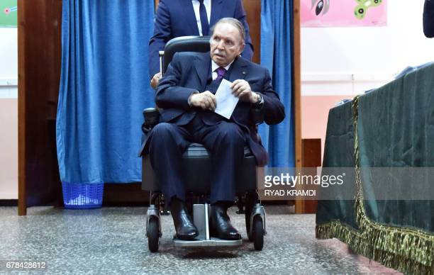 Algerian President Abdelaziz Bouteflika is seen on a wheelchair as he casts his vote at a polling station in Algiers on May 4, 2017 during...