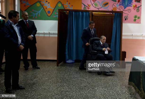 Algerian President Abdelaziz Bouteflika is seen on a wheelchair as he casts his vote at a polling station in Algiers on May 4 2017 during...