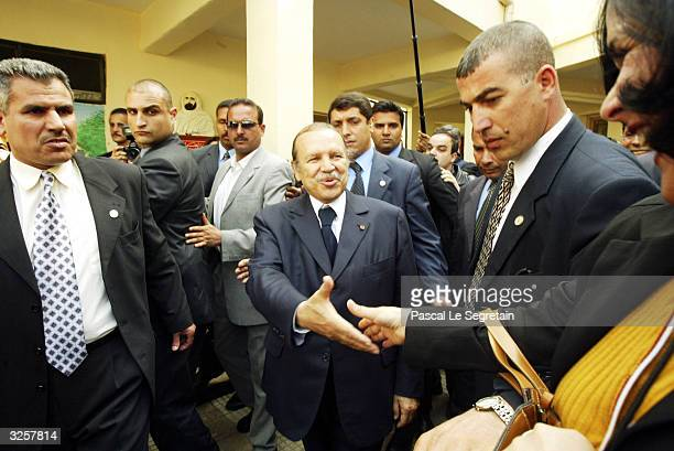 Algerian President Abdelaziz Bouteflika shakes hand with a supporter as he leaves a polling station after voting in the presidential election April 8...