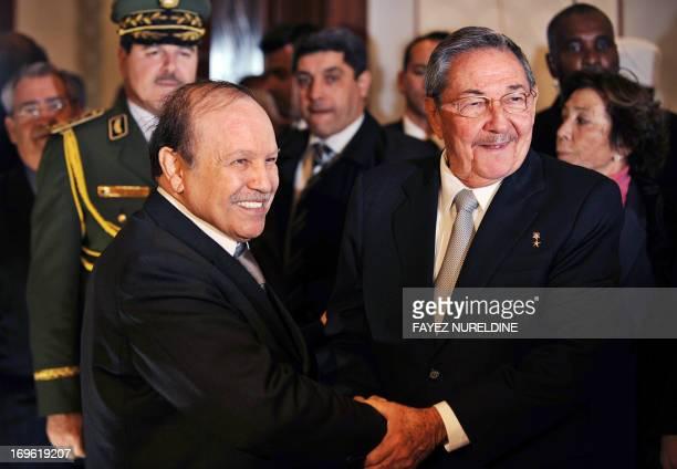 Algerian President Abdelaziz Bouteflika shakes hand with his Cuban counterpart Raul Castro during their meeting at Hourai Boumediene International...