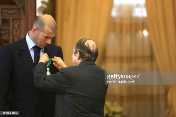 Algerian President Abdelazziz Bouteflika awards French football star Zinedine Zidane with the AlAthir medal Algeria's highest distinction during a...