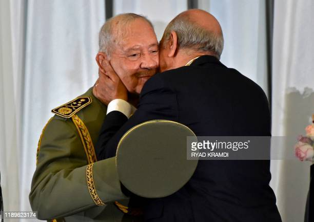 Algerian President Abdelmadjid Tebboune embraces and kisses armed forces chief Lieutenant general Ahmed Gaid Salah during the formal swearingin...