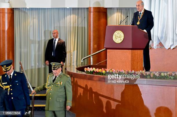 Algerian President Abdelmadjid Tebboune gives an address while armed forces chief Lieutenant general Ahmed Gaid Salah walks below during the formal...
