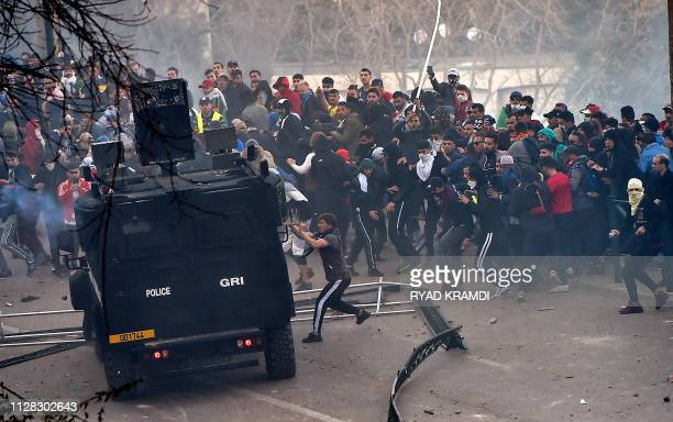 Algerian protesters attempt to overturn a riot police vehicle during clashes in the capital Algiers on March 1 against ailing President Abdelaziz...
