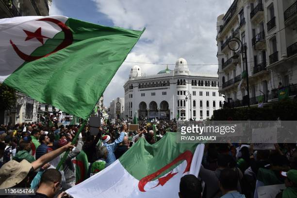 Algerian protesters carry giant national flags as they take part in an antigovernment demonstration in front of La Grande Post in the centre of the...