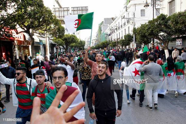 Algerian protesters draped in national flags march during a mass demonstration against ailing President Abdelaziz Bouteflika in the capital Algiers...