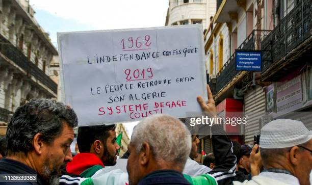 Algerian protesters draped in national flags march with protest signs during a demonstration against ailing President Abdelaziz Bouteflika in the...