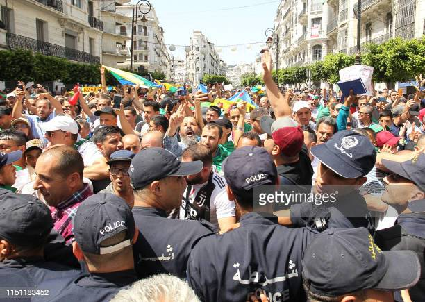 Algerian protesters face a cordon of police during the weekly Friday demonstration in the capital Algiers on June 21 2019 Hundreds of Algerian...