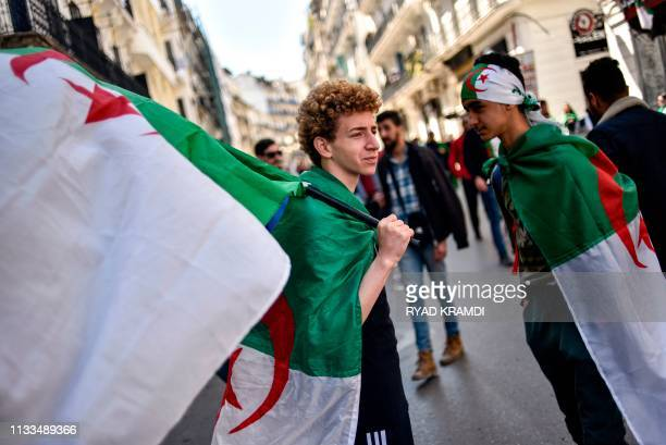 Algerian protesters march draped in and carrying national flags during a demonstration against ailing President Abdelaziz Bouteflika in the capital...
