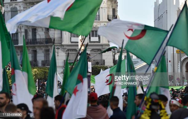 Algerian protesters march draped in national flags during a demonstration against ailing President Abdelaziz Bouteflika in the capital Algiers on...