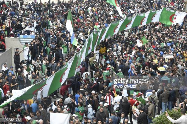 Algerian protesters march national flags during their weekly anti-government demonstration in the capital Algiers, on February 21, 2020.