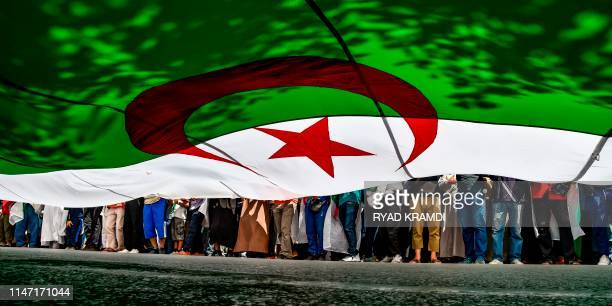 TOPSHOT Algerian protesters march with a giant national flag during a demonstration in the capital Algiers on May 31 2019 Protesters are looking to...
