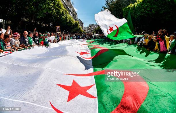 Algerian protesters march with a giant national flag during a demonstration in the capital Algiers on May 31 2019 Protesters are looking to keep up...