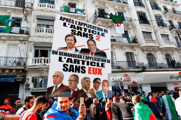 Algerian protesters march with protest signs as they gather during a mass demonstration against ailing President Abdelaziz Bouteflika in the capital...